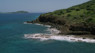 AX102_129 - 5k stock footage aerial video Following a coast with vegetation and sapphire blue waters, Culebra, Puerto Rico