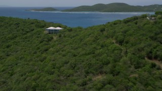 AX102_138 - 5k stock footage aerial video of a Hilltop home along sapphire blue waters, reveal coastal town, Culebra, Puerto Rico