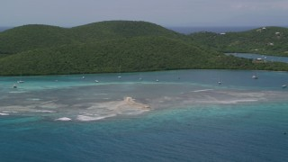 AX102_140 - 5k stock footage aerial video of Sailboats in turquoise waters along a tree covered coast, Culebra, Puerto Rico