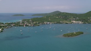 AX102_142 - 5k stock footage aerial video of Sail boats in sapphire blue water near a coastal town, Culebra, Puerto Rico