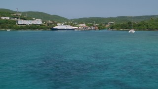 AX102_149 - 5k stock footage aerial video of a Docked ferry in sapphire blue waters by the coast, Culebra, Puerto Rico
