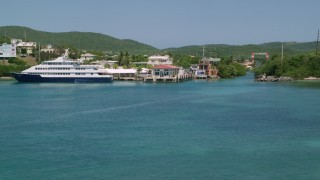 AX102_150 - 5k stock footage aerial video Flying low over sapphire waters toward a waterfront town, and Culebra, Puerto Rico