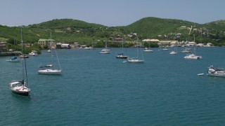 AX102_162 - 5k stock footage aerial video of Sailboats in sapphire waters approaching a coastal town, Culebra, Puerto Rico