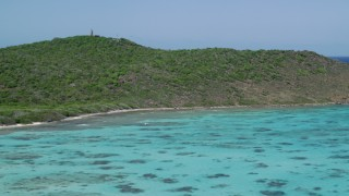 AX102_175 - 5k stock footage aerial video of Turquoise waters along an island's coast, Culebrita, Puerto Rico