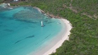 AX102_180 - 5k stock footage aerial video of Boats in turquoise blue water along a white sand beach, Culebrita, Puerto Rico