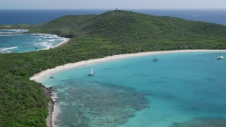 AX102_182 - 5k stock footage aerial video of Catamarans in turquoise blue waters along a white sand Caribbean beach, Culebrita, Puerto Rico
