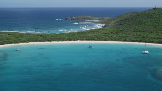AX102_183 - 5k stock footage aerial video of Catamarans in turquoise waters along a white sand Caribbean beach, Culebrita, Puerto Rico