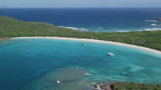 AX102_184 - 5k stock footage aerial video of Catamarans in turquoise waters along a white sand Caribbean beach, Culebrita, Puerto Rico