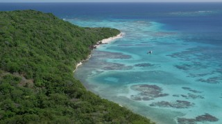 AX102_185 - 5k stock footage aerial video of turquoise waters and reefs along a tree filled coast, Culebrita, Puerto Rico