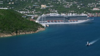 AX102_200 - 5k stock footage aerial video of a Cruise ship docked in sapphire blue waters along a coastal town, Charlotte Amalie, St. Thomas