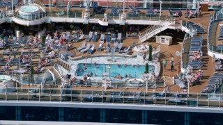 AX102_204 - 5k stock footage aerial video of a Populated pool area on a cruise ship, Charlotte Amalie, St. Thomas