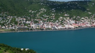 AX102_208 - 5k stock footage aerial video of a Coastal town on a hillside along sapphire waters, Charlotte Amalie, St. Thomas