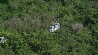 AX102_211 - 5k stock footage aerial video of Gondolas above trees and hillside homes, Charlotte Amalie, St. Thomas