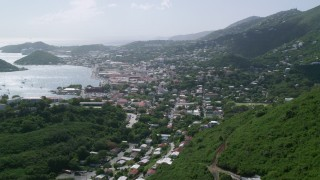 AX102_214 - 5K stock footage aerial video of a Coastal town seen from the hills toward the ocean, Charlotte Amalie, St. Thomas
