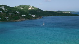 AX102_234 - 5k stock footage aerial video of a Sailboat in sapphire blue waters along oceanfront homes, Southside, St Thomas