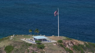 AX102_251 - 5K stock footage aerial video Orbiting an oceanfront guesthouse and American flag, Little St James Island, St Thomas