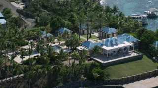 AX102_253 - 5K stock footage aerial video of an Oceanfront mansion and palm trees on turquoise blue waters, Little St James Island, St Thomas