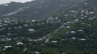 AX102_260 - 5k stock footage aerial video of Hilltop homes among trees, East End, St Thomas