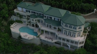 AX102_265 - 5K stock footage aerial video of a Hillside oceanfront mansion and sapphire blue waters, Northside, St Thomas