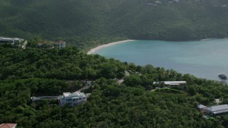 AX102_268 - 5k stock footage aerial video of a Caribbean beach along turquoise blue waters, Magens Bay, St Thomas