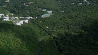 AX102_289 - 5k stock footage aerial video of Condominiums on a hillside surrounded by trees, Northside, St Thomas