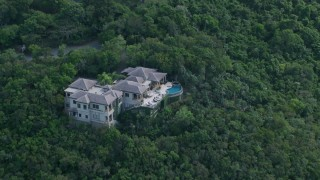 AX102_290 - 5k stock footage aerial video of Hillside mansion surrounded by trees, Northside, St Thomas