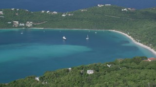 AX102_301 - 5K stock footage aerial video of a Caribbean beach against tree covered hillside and turquoise blue waters, Magens Bay, St Thomas