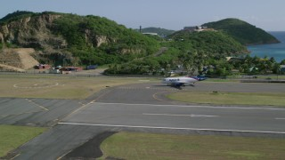 AX103_001 - 5k stock footage aerial video of a jet at Cyril E King Airport along Caribbean blue waters, St Thomas