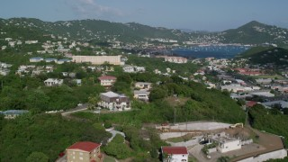 AX103_002 - 5k stock footage aerial video Flying over homes in hills of coastal town, Charlotte Amalie, St Thomas