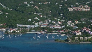 AX103_018 - 5k stock footage aerial video of a Coastal town and boats in the harbor of Caribbean blue waters, Cruz Bay, St John