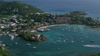 AX103_024 - 5k stock footage aerial video of Grande Bay Resort in the Caribbean blue harbor waters with boats, Cruz Bay, St John