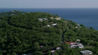 AX103_032 - 5k stock footage aerial video of Ocean view homes on a green hillside, Cruz Bay, St John