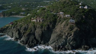 AX103_036 - 5k stock footage aerial video of a Cliff top mansions and sapphire blue Caribbean waters, Cruz Bay, St John