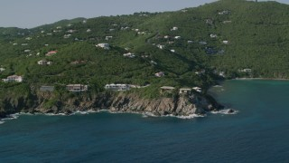 AX103_037 - 5k stock footage aerial video of Hillside mansions overlooking Caribbean blue waters, Cruz Bay, St John