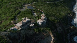 AX103_040 - 5k stock footage aerial video of a Cliff top mansion and Caribbean blue ocean view, Cruz Bay, St John