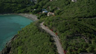 AX103_042 - 5k stock footage aerial video of a Coastal road and mansions along Caribbean blue waters, Cruz Bay, St John