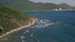 AX103_044 - 5k stock footage aerial video of a Caribbean beach along sapphire blue waters and tree covered hills, Reef Bay, St John