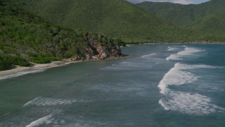 AX103_045 - 5k stock footage aerial video of a Caribbean beach along jungle and Caribbean blue waters, Reef Bay, St John