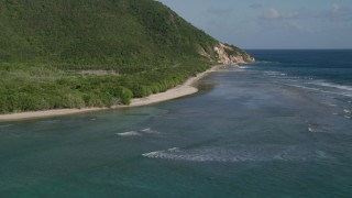 AX103_046 - 5k stock footage aerial video of a Caribbean beach along jungle and sapphire blue Caribbean waters, Reef Bay, St John