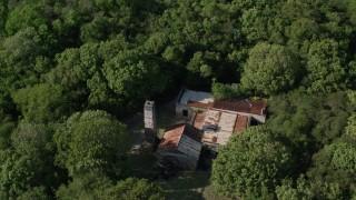 AX103_047 - 5k stock footage aerial video of a Reef Bay Rum Factory Ruins nestled among trees, St John, US Virgin Islands