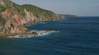 AX103_050 - 5k stock footage aerial video of Coastal cliffs along sapphire blue Caribbean waters, Central, St John