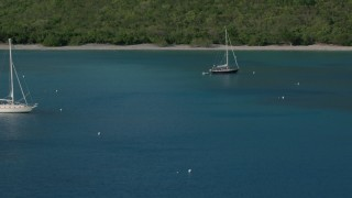 AX103_053 - 5k stock footage aerial video of a Sailboat on Caribbean blue waters of Great Lameshur Bay, St John