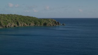 AX103_056 - 5k stock footage aerial video of a Tree covered rugged coast along blue waters of Great Lameshur Bay, St John