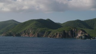 AX103_057 - 5k stock footage aerial video of Coastal cliffs and jungle along sapphire blue Caribbean waters, Central, St John