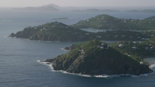 AX103_060 - 5k stock footage aerial video of a Hilltop and cliff top mansions along Caribbean blue waters, Cruz Bay, St John