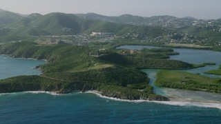 AX103_066 - 5k stock footage aerial video of Tree covered cliffs near coastal town in Caribbean blue waters, East End, St Thomas