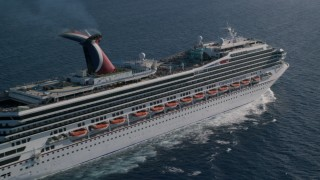 AX103_070 - 5K stock footage aerial video of a Carnival cruise ship in sapphire blue Caribbean waters, St Thomas