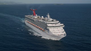 AX103_071 - 5k stock footage aerial video of a Cruise ship in sapphire blue Caribbean waters off the coast, St Thomas
