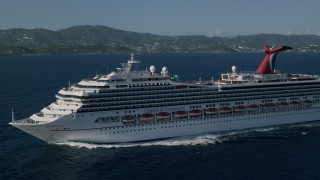 AX103_072 - 5k stock footage aerial video of a Carnival cruise ship in Caribbean blue waters, St Thomas