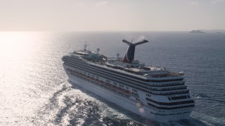 AX103_073 - 5k stock footage aerial video of Carnival cruise ship in Caribbean blue waters, St Thomas